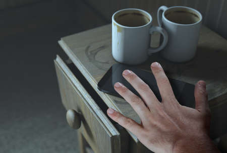 A bed side table with coffee mugs and a generic smartphone and a hand touching it - 3D Render