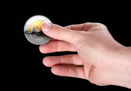 A male hand holding a physical monero cryptocurrency in gold and silver coin form on a dark studio background Stock Photo