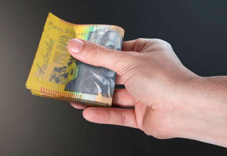 A male hand handing over a wad of folded australian dollar bank notes on an isolated background