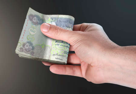 A male hand handing over a wad of folded dubai dirham bank notes on an isolated background