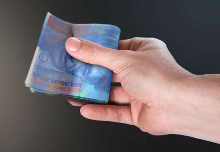 A male hand handing over a wad of folded swiss franc bank notes on an isolated background