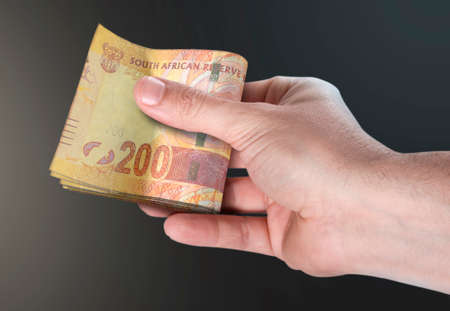 A male hand handing over a wad of folded south african rand bank notes on an isolated background Stock Photo