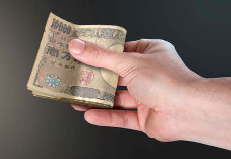 A male hand handing over a wad of folded japanese yen bank notes on an isolated background
