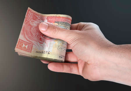 A male hand handing over a wad of folded hong kong dollar bank notes on an isolated background
