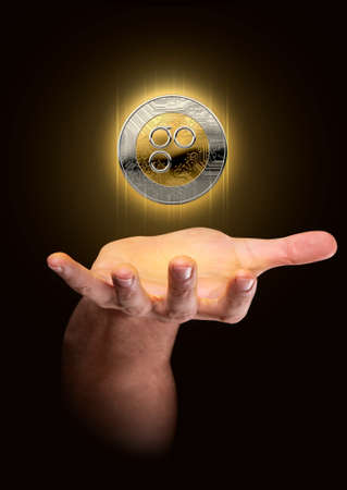 A male hand conjuring up a floating omisego cryptocurrency hologram in gold and silver physical coin form on a dark studio background Stock Photo