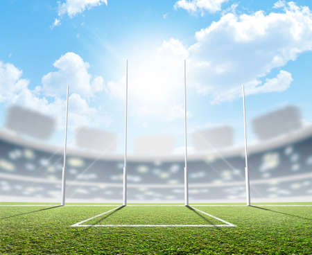 An aussie rules football stadium with a marked green grass pitch and goal posts in the daytime under a blue sky - 3D render