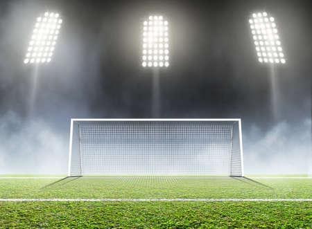 Uno stadio di calcio con un passo marcato dell'erba verde e pali nella notte sotto i riflettori illuminati - 3D rendono