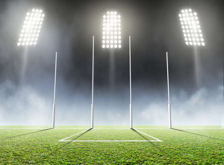 An aussie rules football stadium with a marked green grass pitch and goal posts in the nighttime under illuminated floodlights - 3D render