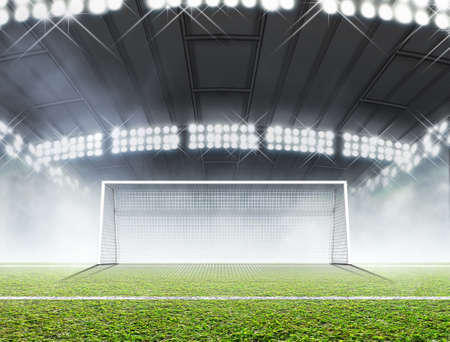 A soccer stadium with a marked green grass pitch and goal posts in the nighttime under illuminated floodlights - 3D render Stock Photo