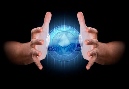 enveloping: A pair of male hands enveloping a hologram of an ethereum coin on an isolated dark background Stock Photo