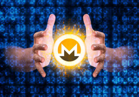 A pair of male hands reaching through digital numerical data figures grasping at a monero coin hologram Stock Photo