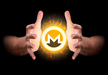 A pair of male hands reaching through the dark grasping at a monero coin hologram Stock Photo
