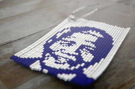 A traditional zulu beaded keyring depicting nelson mandela on an isolated wood background - 3D render Editorial