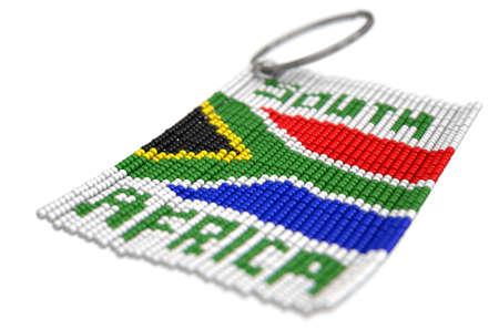 Un portachiavi in ??rilievo zulu tradizionale con le parole e la bandiera della Sudafrica su un fondo bianco isolato - 3D rendono Archivio Fotografico - 88704818
