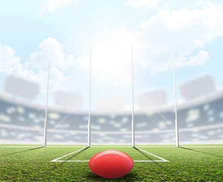 An aussie rules football stadium with a ball and goal posts in the daytime under a blue sky - 3D render Stock Photo