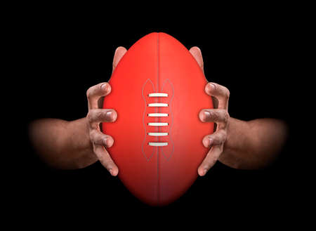 A pair of male hands clamping an aussie rules football on an isolated dark background - 3D render