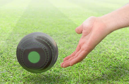 A male hand bowling and releasing a wooden lawn bowling ball on a green lawn grass surface -3D render Stock Photo
