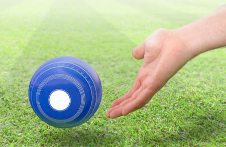 A male hand bowling and releasing a blue wooden lawn bowling ball on a green lawn grass surface -3D render