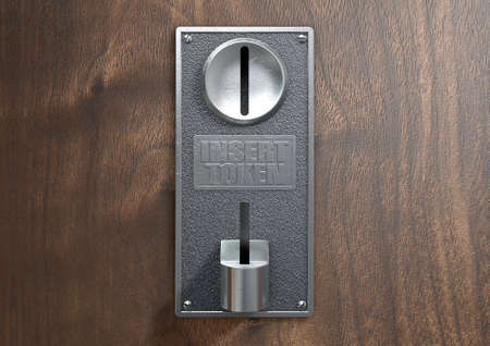 A vintage metal coin receptacle slot panel from a coin operated machine with entry and exit slots mounted on a wooden surface
