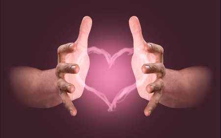 A pair of male hands conjuring up a pink heart shaped vapor on an isolated dark studio background Stock fotó