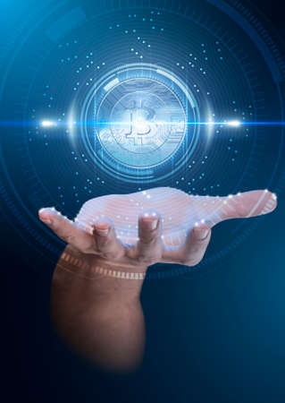 A male hand conjuring up a floating blue bitcoin cryptocurrency hologram on a dark studio background overlaid with a technical data analysis interface