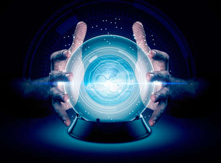 A pair of male hands surrounding a crystal ball conjuring up a ripple crytocurrency hologram on an isolated dark studio background Archivio Fotografico