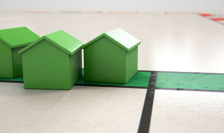 A closeup of green plastic house icon on a game board - 3D render