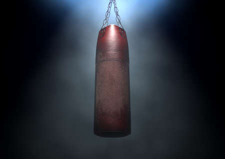 An old worn red leather punching bag hanging by chains in a  dark room lit by an ethereal spotlight - 3D render Stock Photo