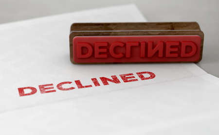 A wooden stamp with embossed text stamping the word declined on a form - 3D render