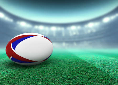 A reguar white rugby ball with red and blue design elements resting on a stadium grass pitch at night under illuminated floodlights - 3D render
