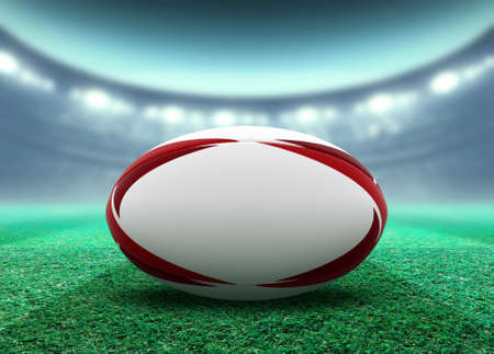 A reguar white rugby ball with red design elements resting on a stadium grass pitch at night under illuminated floodlights - 3D render
