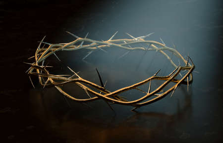 Branches of thorns woven into a gold crown depicting the crucifixion on a dark spotlit background - 3D render
