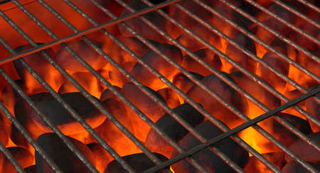 A direct top view of burning hot coal in a barbecue stand covered by a regular iron bar grill - 3D render 스톡 콘텐츠