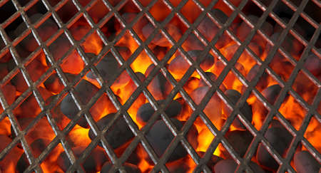A direct top view of burning hot coal in a barbecue stand covered by diamond patterned iron grill - 3D render Stock Photo