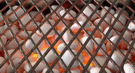 A direct top view of burning hot coal and white ash in a barbecue stand covered by diamond patterned iron grill - 3D render Stock Photo