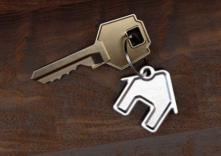 A brass key attached to a cast iron keyring in the shape of a house on an isolated wooden surface background - 3D render