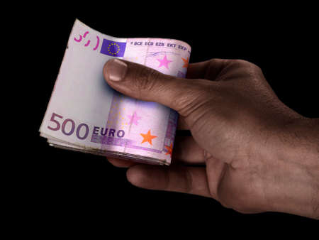 A black male hand handing over a wad of folded european euro bank notes on an isolated background