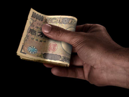 A black male hand handing over a wad of folded Japan Yen bank notes on an isolated background