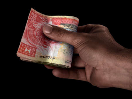 A black male hand handing over a wad of folded Hong Kong Dollar bank notes on an isolated background Banco de Imagens