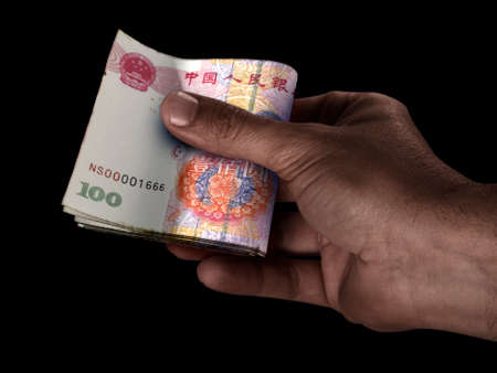 A black male hand handing over a wad of folded China yuan bank notes on an isolated background Imagens