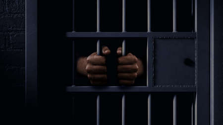A closeup of a dimly lit prison holding cell door with a pair of african black hands holding onto the bars
