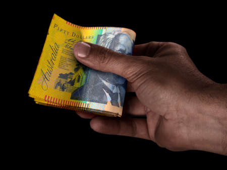A black male hand handing over a wad of folded australian dollar bank notes on an isolated background