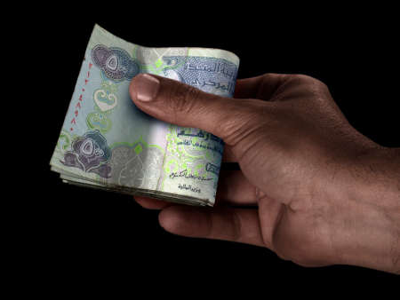 A black male hand handing over a wad of folded dubai dirham bank notes on an isolated background