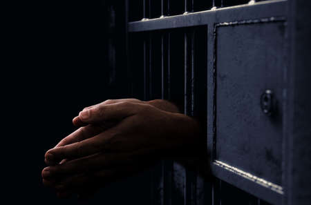 A closeup of a dimly lit prison holding cell door with a pair of african black hands reaching out in a clenched prayer position Stock Photo