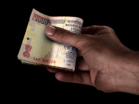 A black male hand handing over a wad of folded India Rupee bank notes on an isolated background