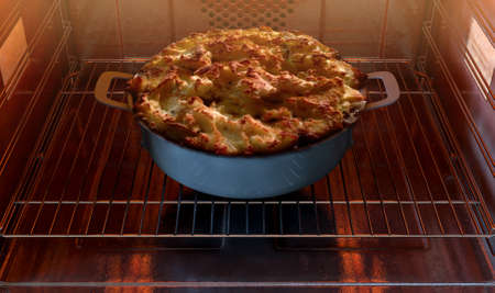 A close view of a cottage pie in a pot inside a hot household oven   - 3D render Stock Photo
