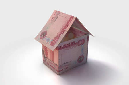 A concept of UAE dirham bank notes folded into the shape of a simple house on an isolated background - 3D render Stock Photo