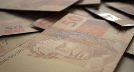 A close-up view of a scattered pile of brazilian real banknotes - 3D render