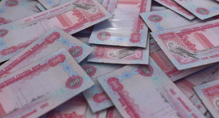 A close-up view of a scattered pile of UAE dirham banknotes - 3D render Imagens