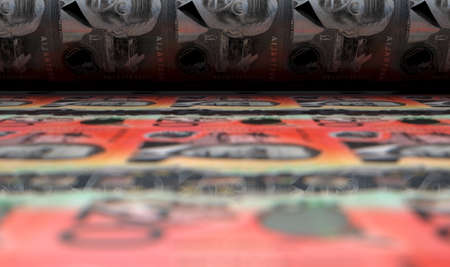 A concept image showing a sheet of new Australian dollar notes going through a roller in its final phase of a print run - 3D render Imagens
